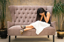 Beautiful Woman With Dark Hair In A White Skirt Sits On The Sofa With Her Face Buried In Her Palms