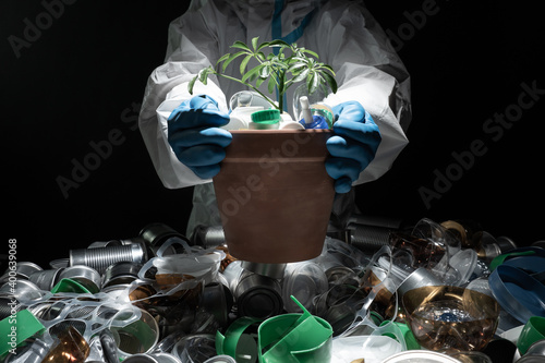 Fotografie, Obraz Environmentalist in protective suit holding young seedling in pot full of plastic dirt trash