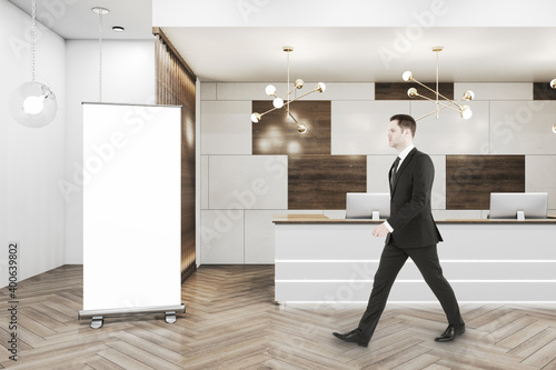Businessman walking in office hall Poster Mural XXL