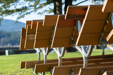 A Close View Of Sunlit Park Picnic Benches Inter-stacked Against Each Other With An Out Of Focus Park Background
