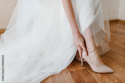 Canvas Bride putting on her stylish classic lacquered beige shoes