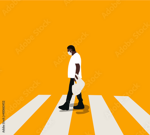 Fotografiet Man in a protective mask crosses the road at a pedestrian crossing