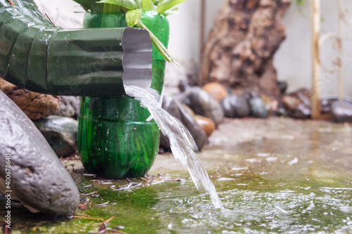 Obraz na plátně Rain water is pouring from the green draining gutter on the mossy ground, select