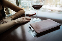 Hundred Dollars Generous Tip On The Table In A Leather Folder. The Girl Drank The Wine And Paid The Bill. Large Wine Glass On The Table In An Expensive Restaurant. The Girl Is Waiting For The Waiter.