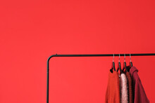 Rack With Clothes On Color Background