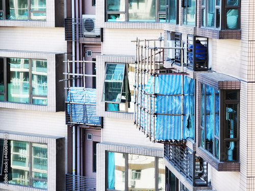 Fotografia worker protected by bamboo scaffolding repair or replace air conditioner above window outside high rise residential building in Hong Kong