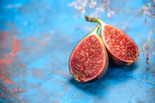 Front Close View Of Fresh Black Mission Figs On Blue Background Stock Photo