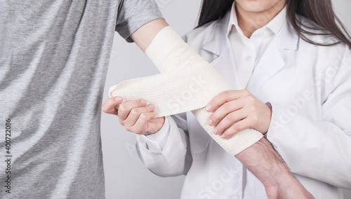 Fotografering Caucasian doctor putting bandage on patient hand.