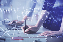 Multi Exposure Of Woman Hands Typing On Computer And Financial Chart Hologram Drawing. Stock Market Analysis Concept.