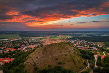 Sumeg, Hungary - Aerial Panoramic View Of The Famous High Castle Of Sumeg In Veszprem County At Sunset With Storm Clouds And Dramatic Colors Of Sunset At Background On A Summer Afternoon