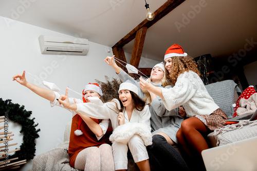 Obraz na plátně Group of happy women girls friends in Christmas santa hats and face masks take a