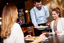 Young Waiter Serving Food To Female Customers In The Restaurant