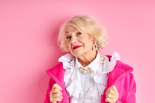 Fancy Aged Lady Posing At Camera Wearing Pink Coat And White Blouse Isolated Over Pink Background