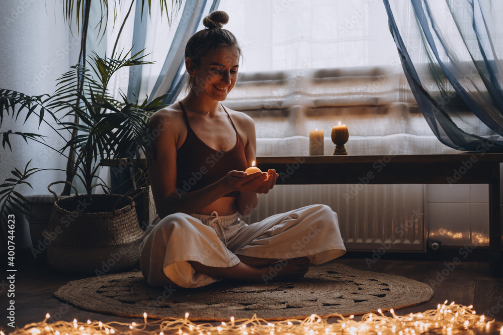 Fototapeta Young woman sitting on the floor, lights candles, enjoy meditation, do yoga exercise at home. Mental health, self care, No stress, healthy habit, mindfulness lifestyle, anxiety relief concept