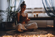 Young woman sitting on the floor, lights candles, enjoy meditation, do yoga exercise at home. Mental health, self care, No stress, healthy habit, mindfulness lifestyle, anxiety relief concept