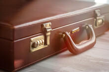 Vintage Brown Suitcase Close Up  View On A Grey  Background With Sunlight Bokeh