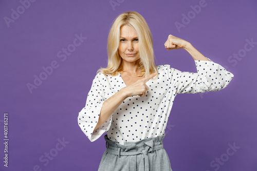 Stampa su Tela Strong elderly gray-haired blonde woman lady 40s 50s years old in white dotted blouse pointing index finger on biceps muscles looking camera isolated on bright violet color background studio portrait