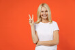 Smiling funny elderly gray-haired blonde woman lady 40s 50s years old in white casual t-shirt standing showing victory sign looking camera isolated on bright orange color background studio portrait.