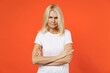 Leinwandbild Motiv Displeased worried elderly gray-haired blonde woman lady 40s 50s years old in white casual t-shirt standing holding hands crossed looking camera isolated on bright orange background studio portrait.