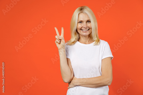 Obraz Smiling funny elderly gray-haired blonde woman lady 40s 50s years old in white casual t-shirt standing showing victory sign looking camera isolated on bright orange color background studio portrait. - fototapety do salonu