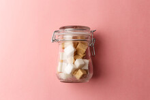 Jar With White Sugar Cubes And Brown Cane Sugar Lump On Pastel Pink Background. Dry Food Product On Home Kitchen