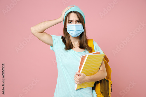 Tablou Canvas Worried young woman student in t-shirt hat backpack face mask to safe from coronavirus virus covid-19 put hand on head isolated on pink background