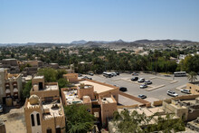 View Of A Parking Lot And Some Buildings And Palm Trees That Surround Bahla Fort. Bahla, Oman.