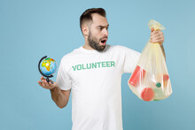 Shocked Disturbed Young Man In White Volunteer T-shirt Hold Trash Bag World Earth Globe Isolated On Blue Background Studio Portrait. Voluntary Free Assistance Help Trash Sorting Recycling Concept.