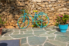 A Blue And Yellow Bicycle Leaning Against A Stone Wall, Folegandros Island, Greece.