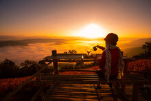 The Silhouette Of A Woman Sitting In Front Of The Sunrise On The Hill With The Sea Of ​​clouds In The North Of Thailand, Doi Samer Dao, Nan Province