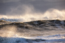Rough Surf Under Dark Ominous Storm Clouds, With Spray Coming Off Large Waves Breaking.