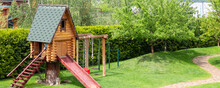 Small Wood Log Playhouse Hut With Stairs Ladder And Wooden Slide On Children Playground At Park Or House Yard. Green Grass Lawn Garden And Paved Pathway Background On Bright Sunny Day. Panoramic View