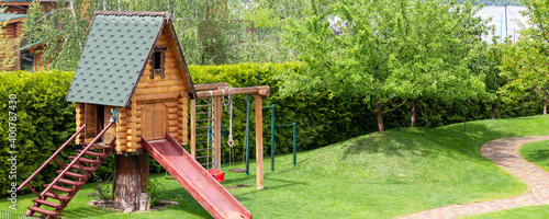 Fotografie, Tablou Small wood log playhouse hut with stairs ladder and wooden slide on children playground at park or house yard