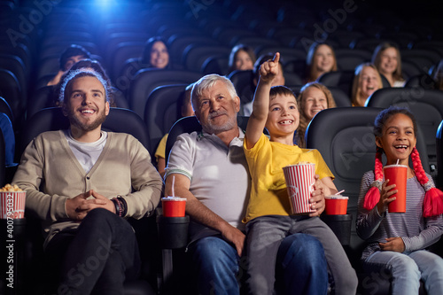 Obraz Grandfather with grandson enjoying cartoon in cinema hall. - fototapety do salonu
