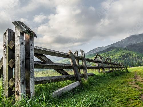 Obraz Stary płot pastwiska na tle gór i zachmurzonego nieba o poranku - fototapety do salonu