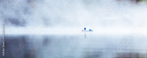 Photo the lonely fisher in the mist, early morning a fisher man wit his boat  surround
