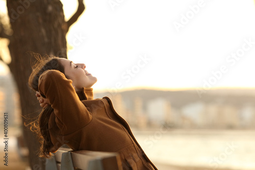 Foto Woman resting sitting on a bench on the beach in winter