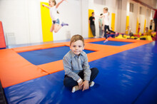 Healthy Little Boy Sitting On Trampoline Among Jumping Kids Indoors In Leisure Activity Club