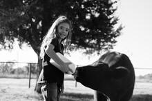 Young Girl Bottle Feeding Calf On Farm, Chores Show Rural Caretaking Lifestyle.