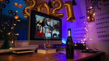 Celebrating Virtual Christmas New Year's Eve Party 2021 At Home During Covid-19 Pandemic. Couple Holding And Toasting Champagne Glasses How To Celebrate And Decorate Foiled Balloons Of 2021.