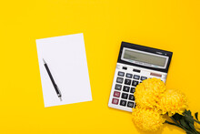 Large Silver Calculator, Black Pen, Clean Sheet Of Paper And Flower Bouquet Lays On A Yellow Background. Concept Of Business Holiday And Congratulating Women On Women's Day At The Workplace. March 8