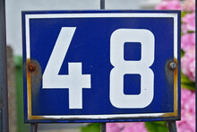 A Blue House Number Plaque, Showing The Number Forty Eight (48)