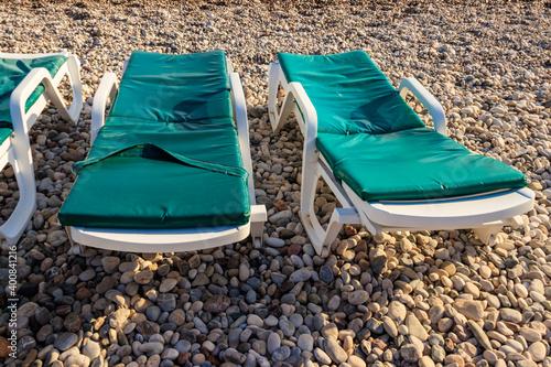 Slika na platnu Chaise lounges on a pebble beach