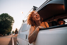 Happy Young Woman Leaning Out Of Van Window
