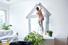 Young Woman Making House With Paint Roller On Wall While Standing On Ladder At Home