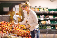 Teenage Girl Wearing Protectice Mask And Gloves Choosing Apples At Supermarket