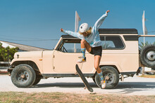 Woman Skateboarding Against Old Vehicle On Sunny Day