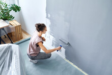 Young Woman With Paint Roller Painting Wall While Crouching At Home