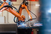 Robotic Arms Welding In Industrial Factory