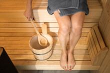 Woman With Wooden Spoon And Bucket Relaxing In Sauna